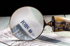 Magnifying jobs in the newspaper. Magnifying the word jobs from a newspaper Stock Photos
