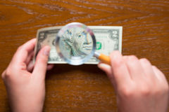 Magnifying lens in hands and two dollars Royalty Free Stock Photos
