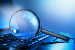 Magnifying lens on the laptop keyboard royalty free stock images