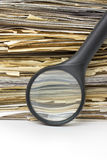 Magnifying lens  on the old files stack background Royalty Free Stock Photography
