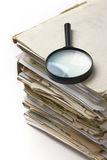 Magnifying lens  on the old paper files. Magnifying lens  on the stack of old files Royalty Free Stock Photos