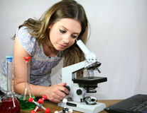 Magnifying the Problem. A biology student uses her microscope and laptop computer stock photography