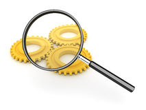Magnifyng glass and yellow gears Royalty Free Stock Photos
