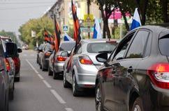 Magnitogorsk, Ρωσία, - 22 Αυγούστου, 2014 Μια ομάδα αυτοκινήτων με τις ρωσικές και σημαίες του ST George σε μια οδό πόλεων στοκ εικόνες
