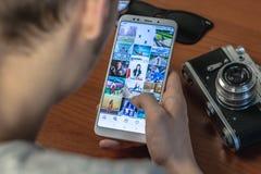 Magnitogorsk, Rússia - 14 de março de 2019: Um homem novo guarda um smartphone com uma aplicação aberta do instagram e imagem de stock royalty free