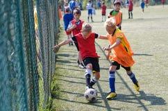 Magnitogorsk, Rosja, - Sierpień, 8, 2014 Chłopiec bawić się futbol w jardzie, ogradzającym z ogrodzeniem metal siatka fotografia stock