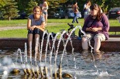 Magnitogorsk, Rusia, - agosto, 22, 2014 Dos muchachas están descansando al lado de la fuente en la plaza fotos de archivo libres de regalías