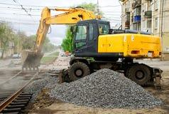 Magnitogorsk, Rusia, - mayo, 17, 2019 El excavador amarillo cae los escombros dormidos reparó los carriles de la tranvía Cruces d foto de archivo libre de regalías