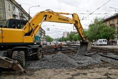 Magnitogorsk, Rusland, - 17 Mei, 2019 Arbeiders en een geel graafwerktuig gegoten puin herstelde tramsporen Kruispunten van Marx  stock fotografie