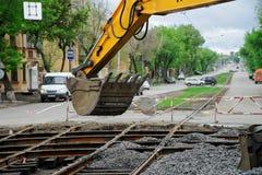 Magnitogorsk, Rusland, - 17 Mei, 2019 Emmer van de gele sporen van de graafwerktuig dalende in slaap puin herstelde tram Kruispun royalty-vrije stock afbeelding