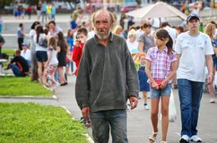Magnitogorsk, Russia, - August, 22, 2014. Elderly homeless man walks among people around the town square. Summer in the city royalty free stock photography