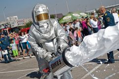 Magnitogorsk, Russia, - August, 7, 2014. Firefighter using foam from a hose extinguishes a fire in the town square. Protective. Suit. Training fire. Caption stock images