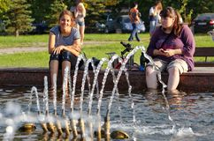 Magnitogorsk, Russia, - August, 22, 2014. Two girls are resting by the fountain in the town square royalty free stock photos