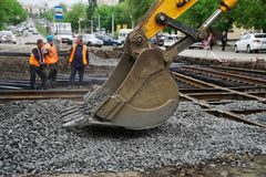 Magnitogorsk, Russia, - May, 17, 2019. Workers and a bucket of yellow excavator falling asleep rubble repaired tram rails. royalty free stock images