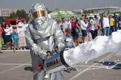 Magnitogorsk, Russland, - August, 7, 2014 Feuerwehrmann setzt heraus ein Feuer in den Marktplatz ein Schutzanzug und Schaum für lizenzfreie stockbilder