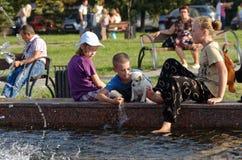 Magnitogorsk, Russland, - August, 22, 2014 Kinder und Hunde spielen nahe dem Brunnen im Marktplatz lizenzfreie stockbilder