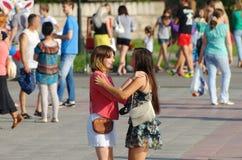 Magnitogorsk Ryssland, - Augusti, 22, 2014 Dans för två flickor bland folk som går i stadfyrkanten royaltyfri foto