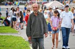 Magnitogorsk Ryssland, - Augusti, 22, 2014 Den äldre hemlösa mannen går bland folk runt om stadfyrkanten Sommar i staden royaltyfri fotografi