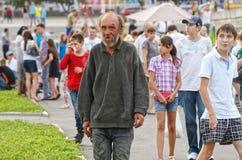 Magnitogorsk Ryssland, - Augusti, 22, 2014 En äldre hemlös man går i en folkmassa runt om en stadsfyrkant Sociala kontraster fotografering för bildbyråer
