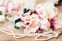Magnolia flowers with pearls on wooden table Royalty Free Stock Images