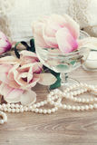 Magnolia flowers with pearls on wooden table Stock Photo