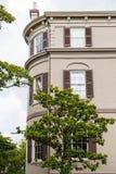 Magnolia par le vieux bâtiment de plâtre de Brown Photographie stock libre de droits