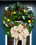 Magnolia Wreath. Natural Christmas wreath made with fresh magnolias leaves, studded with red berries and lemons and tied with a natural burlap ribbon Stock Photo