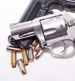 A 357 magnum revolver on top of a 40 caliber pistol with eight 40 caliber hollow point bullets. On a white background stock photo