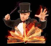 Mago con il libro burning aperto Fotografia Stock Libera da Diritti