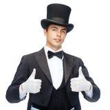 Mago en el sombrero de copa que muestra los pulgares para arriba Foto de archivo libre de regalías