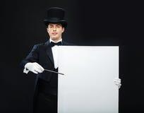 Mago en sombrero de copa con truco mágico de la demostración de la vara Imágenes de archivo libres de regalías