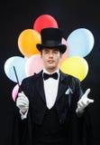 Mago en sombrero de copa con truco mágico de la demostración de la vara Fotos de archivo libres de regalías