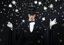 Mago en sombrero de copa con truco mágico de la demostración de la vara Foto de archivo