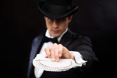 Mago en truco de la demostración del sombrero con los naipes Imagen de archivo libre de regalías