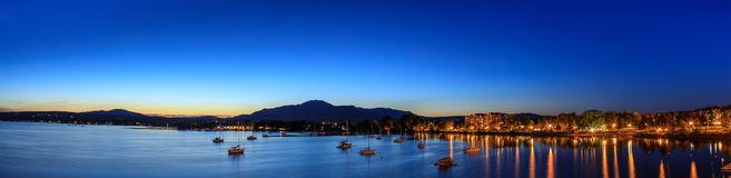 Magog, Province of Quebec, Canada, September 2018. Magog town at. Night in reflections of Memphremagog lake. Canadian romantic landscape with mountains, lake royalty free stock photos