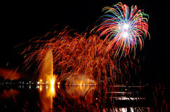 Magrnificient fireworks over a lake. Impressive, bright and colorful fireworks over a lake with lighten water fountain, great celebration background Royalty Free Stock Images