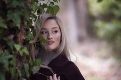 Magro adolescente rubio lindo contra un árbol cubierto con las hojas verdes Fotografía de archivo