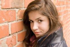 Magro hermoso de la chica joven en la pared de ladrillo roja 2 fotografía de archivo