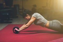 Magro, a menina do halterofilista, faz os exercícios com o rolo para a imprensa no gym imagens de stock
