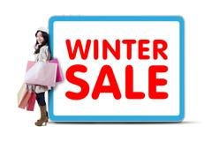 Magro shopaholic femenino en el texto de la venta del invierno Imagen de archivo libre de regalías