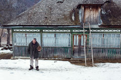 MAGURA, ROMANIA - 05 FEB: Old romanian peasant in front of his old house on February 05 2015. Magura is a village in Carpatian Royalty Free Stock Photography