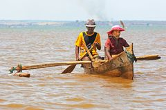 Malagasy family in a small rowing boat. Mahajanga, Madagascar - November 10, 2017: Malagasy family in a small rowing boat. The woman has the face covered by a Royalty Free Stock Images