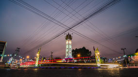 Clock tower evening with traffic lights trails. Mahasarakham clock tower in the evening with traffic lights trails. Shooting the landmark of mahasarakham when Stock Photos