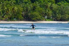 MAHE, SEYCHELLES - SEPTEMBER 25, 2018: Unidentified man surfing on a large wave on island Mahe on the coast of Indian ocean - is. The best surf paradise in stock photos