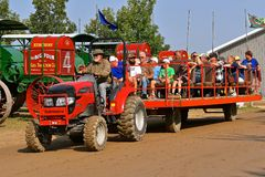 Mahindra tractor pulling people hauler. ROLLAG, MINNESOTA, Sept 3. 2017: A Mahindra tractor pulls a loaded people hauler of visitors at the annual WCSTR farm Stock Photo