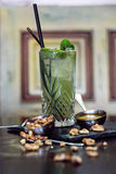 Mahito cocktail with with honey and walnuts on wooden table Royalty Free Stock Image