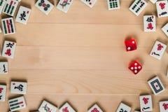mahjong的红色模子和骨头瓦片在浅褐色的木背景 库存图片