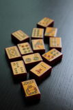Mahjong. Image of vintage enrobed mahjong tiles scattered along a dark cherry wood table Royalty Free Stock Photography