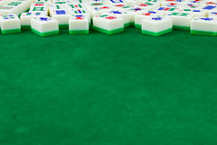 Mahjong Table Background. Chinese card game mahjong tiles randomly laid on green specific mahjong table with a lots of space for using as background Royalty Free Stock Images