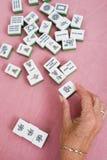 Mahjong tile. Senior woman hand holding a piece of mahjong tile stock image